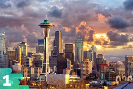 Skyline view of Seattle Washington featuring the Space Needle on a cloudy day with the sun peeking through the clouds.