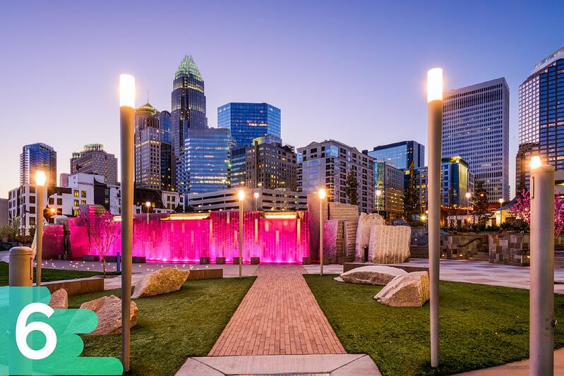 Downtown Charlotte, North Carolina in a park with rocks, grass, and monuments with a pink light on them.
