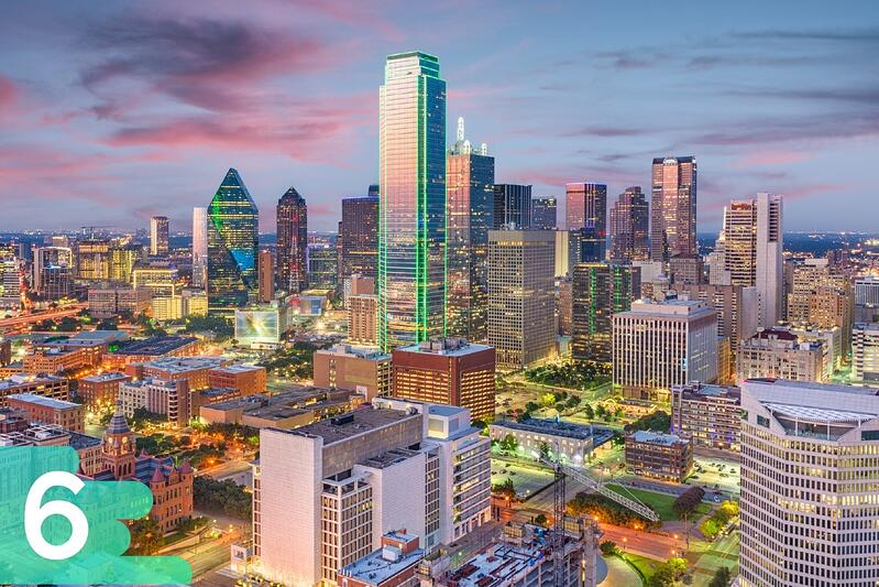 Aerial shot of downtown Dallas, Texas in the evening with each skyscraper lit up and reflecting lights.