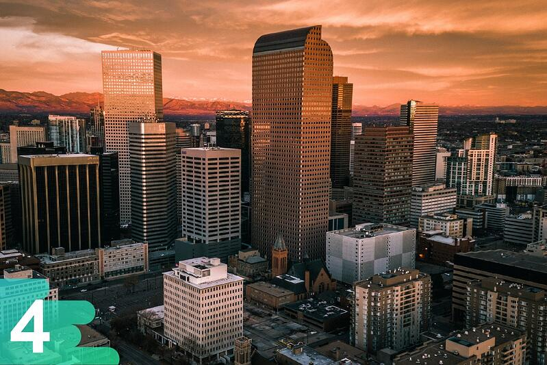 Aerial image of downtown Denver buildings with a burnt orange sunset reflecting off the buildings.