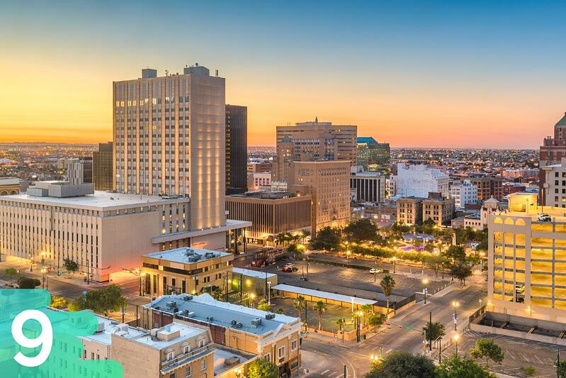 Downtown El Paso, Texas at sunset with the buildings all lit up and traffic lights in the background.