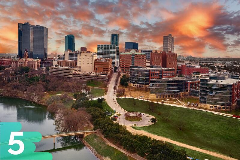 Sunset aerial shot of downtown Fort Worth, Texas, with a waterfront park up front and the buildings toward the back.