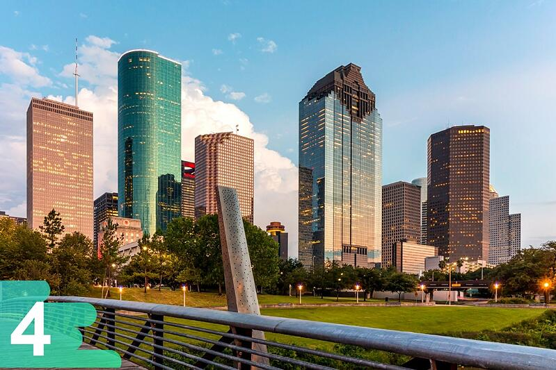 Ground shot from a Houston park featuring the large skyscrapers in the back on a backdrop of a blue partly cloudy day.