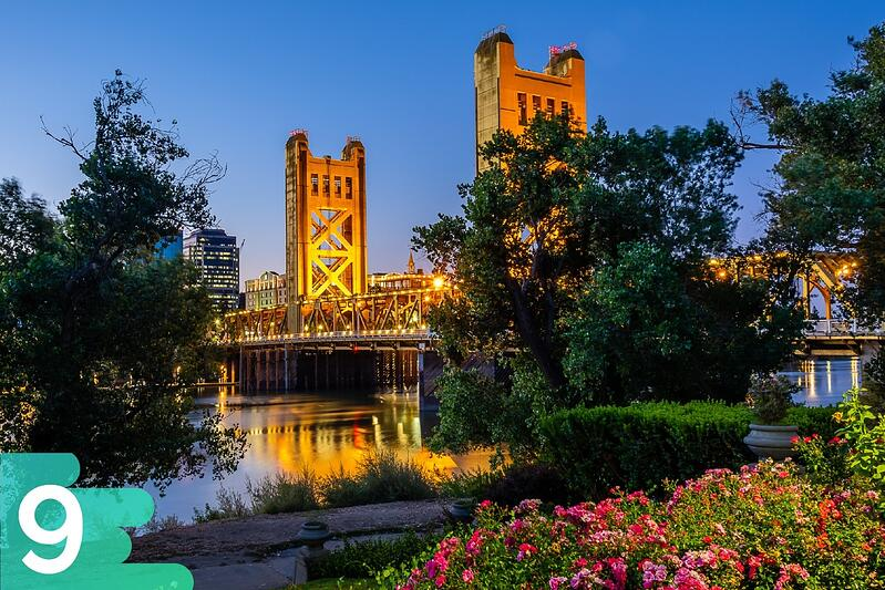 Flower garden in Sacramento with large lit-up bridge in the background leading into downtown Sacramento.